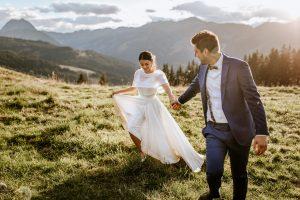 Bräutigam nimmt seine Frau an die Hand und läuft mit ihr auf einer Wiese in Tirol auf den Bergen