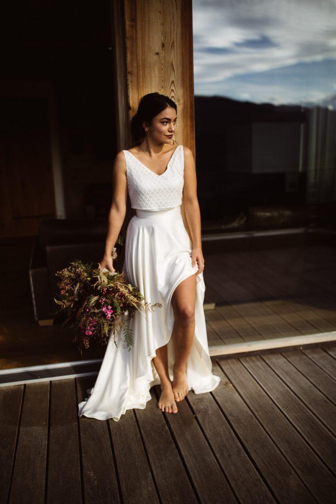 Braut lehnt mit ihrem Brautstrauß und dem weißen Kleid an einem Fenster und wartet auf die Trauung