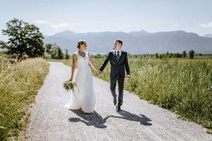 Braut und Bräutigam laufen Hand in Hand auf einem Feldweg beim Gut Kerschlach