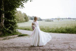 Braut lässt ihr weißes Kleid im Wind wehen
