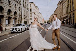 Braut und Bräutigam laufen über die Straßenbahnschiene in München