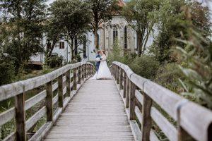 Braut und Bräutigam auf der Brücke vor der Kirche am Kloster Seeon in der Nähe von Schloss Amerang am Chiemsee