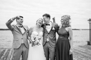 Braut und Bräutigam lachen ausgelassen mit ihren Trauzeugen