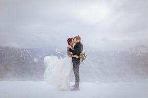 Braut und Bräutigam trotzen Schneesturm bei winterlichen Bedingungen auf dem Berg