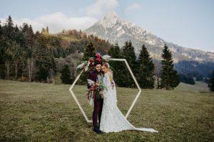 Boho Hochzeitspaar steht vor Traubogen mit Bergpanorama im Allgäu