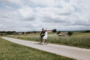 Bräutigam fährt seine Braut auf dem Fahrrad - Hochzeitsfotos am Gögerl in Weilheim