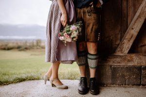 Braut mit Brautstrauß und Hochzeitsdirndl mit Bräutigam in Lederhose / Hochzeit in Bad Kohlgrub