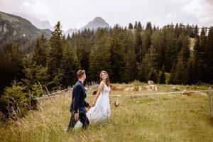 Braut und Bräutigam streifen Hand in Hand durch eine Wiese in den Garmischer Alpen vor dem Kreuzjochhaus