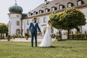 Brautpaar schaut sich nach der Trauung an - Wunderschöne Kulisse vor dem Schloss Höhenried am Starnberger See