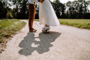 Braut in weißem Kleid mit Chucks steht auf Skateboard