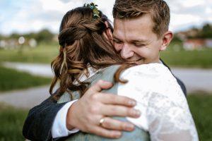 Bräutigam ist nach der Trauung am Staffelsee gerührt und nimmt seine Frau in den Arm