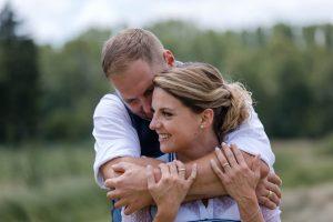 Bräutigam in Tracht umarmt seine Braut in Dirndl