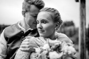 Bräutigam lehnt seinen Kopf an die Schulter seiner zukünftigen Frau in Tracht bei Weilheim