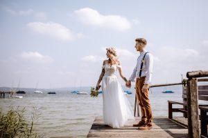 Braut und Bräutigam stehen für ihre Hochzeitsfotos auf einem Steg und schauen auf den Ammersee
