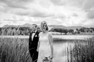 Hochzeit Fotograf am Riegsee - Brautpaar steht am See mit Bergen im Hintergrund