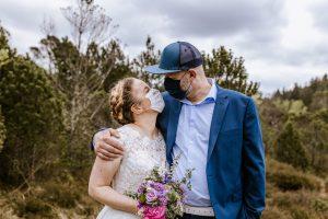Brautpaar küsst sich mit Corona Schutzmaske und Mütze